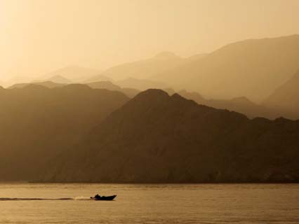 Speedboat Motoring Beneath Silhouetted Mountain Ridges Sloping Towards the Gulf of Oman