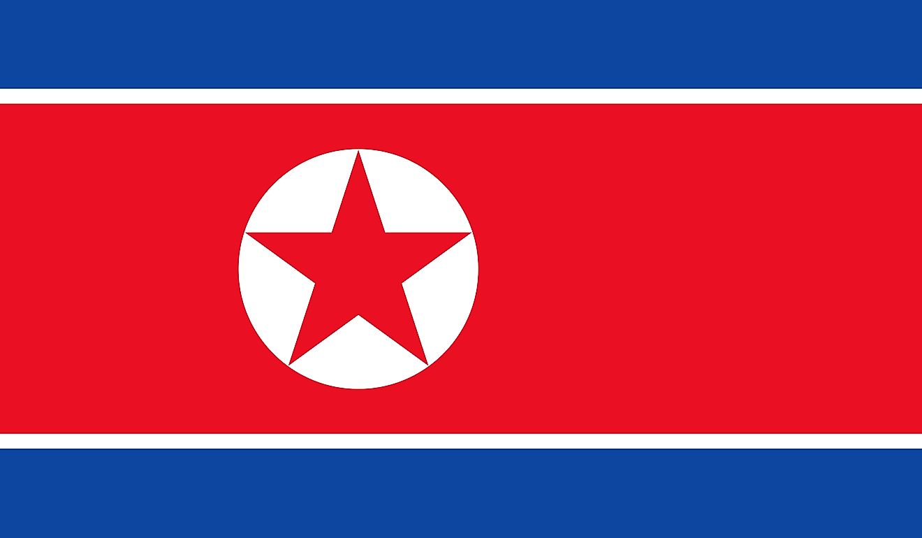 The flag of North Korea features three horizontal bands of blue (top), red (triple width and edged in white), and blue, and a white disk with five-pointed star on the hoist side of the red band