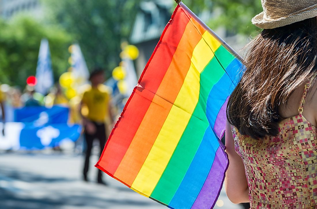 A spectator carries a pride flag at an event.
