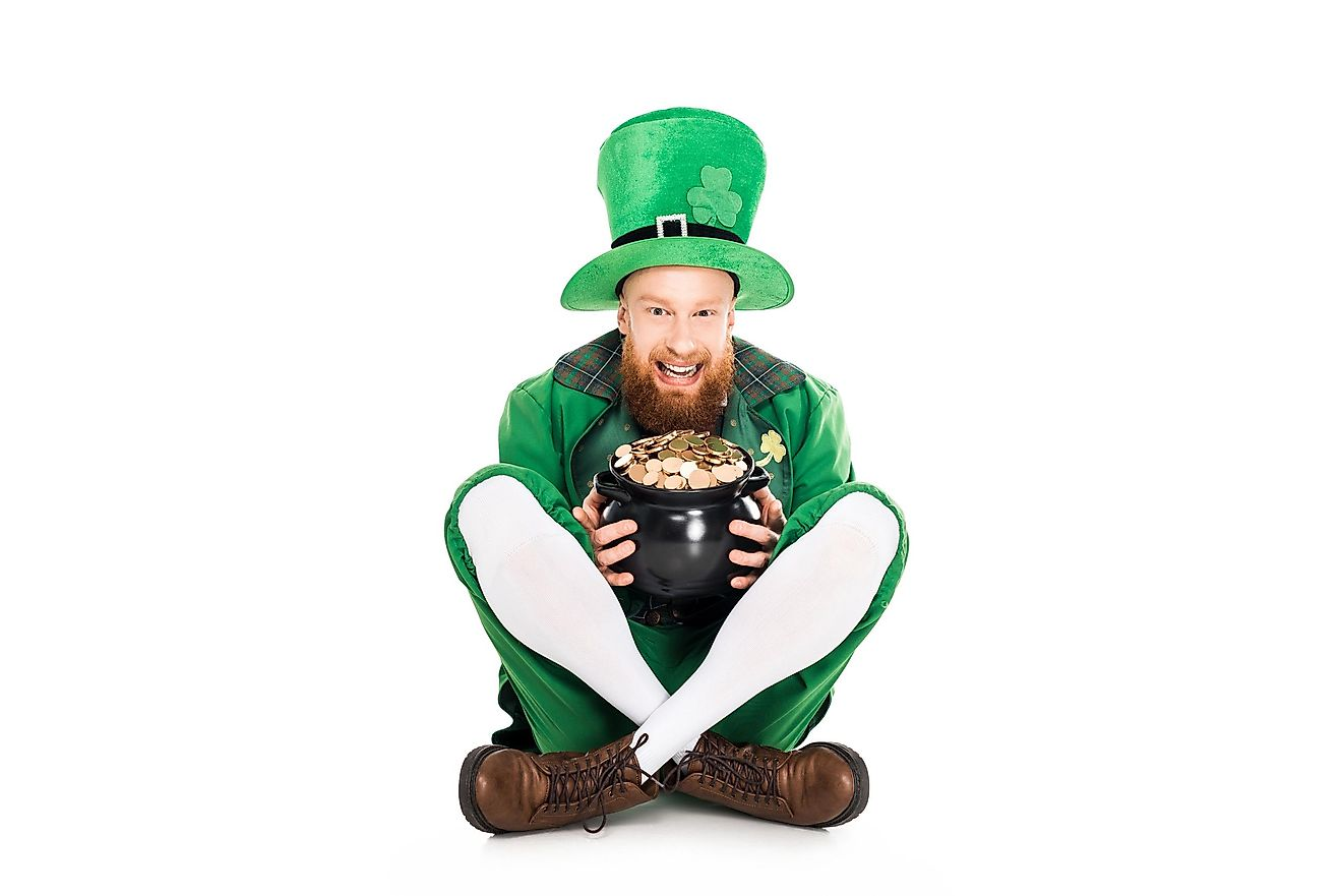 A man dressed as a leprechaun in green suit holding a pot of gold.
