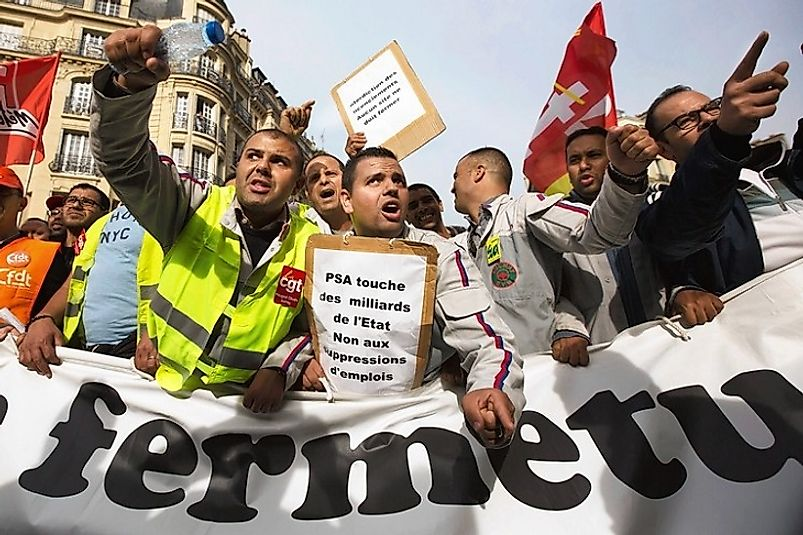 French workers protesting job cuts due to high labor tax costs at their places of employment.