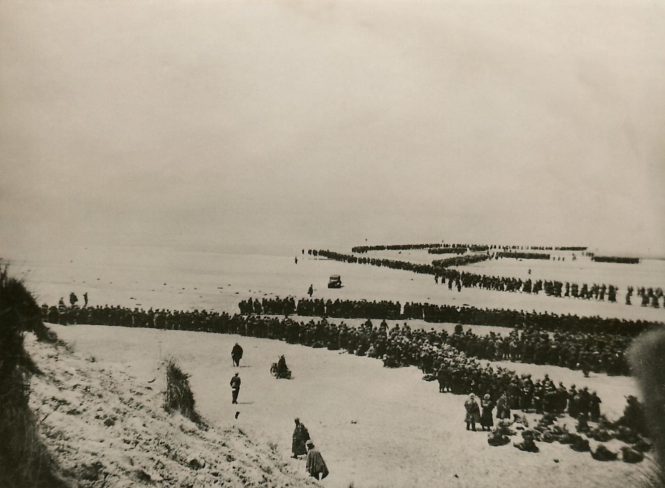 Military evacuation of Dunkirk during World War 2. Thousands of British and French troops wait on the dunes of Dunkirk beach for transport to England.