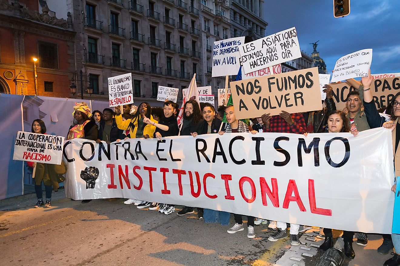 Protestors in Madrid hold up a sign protesting systemic racism. Editorial credit: Magdalena Rydz / Shutterstock.com