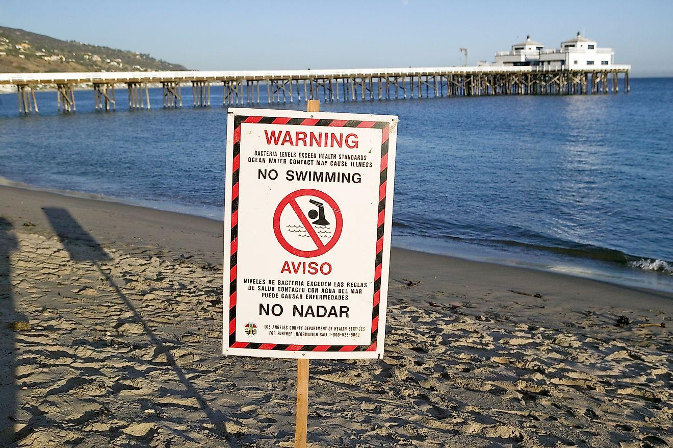 "A ""Warning - No Swimming""sign due to pollution at a Malibu beach, Malibu, California. Image credit: Joseph Sohm/Shutterstock.com"
