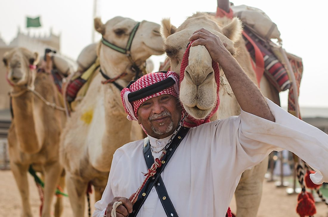 A man in Saudi Arabia with camels. Editorial credit: H1N1 / Shutterstock.com.