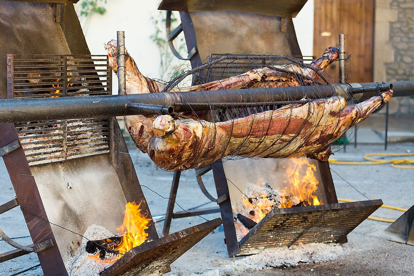 Carcass of whole bull roasting on spit at Medieval Fiesta in Besalu, Spain. Image credit: Iakov Filimonov/Shutterstock.com