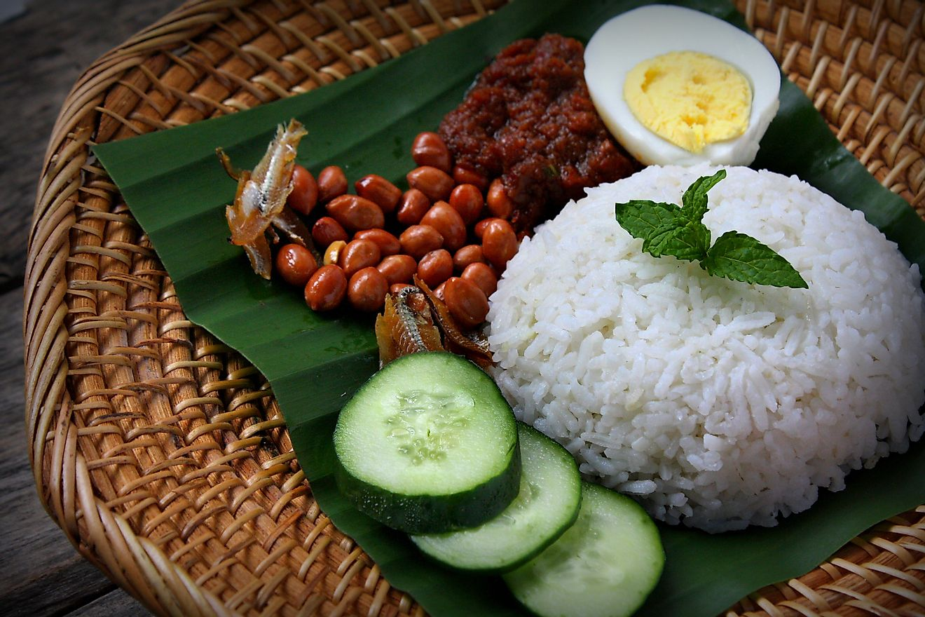 Nasi Lemak, a fragrant rice dish cooked in coconut milk and pandan leaf commonly found in Malaysia. Served with sambal, anchovies, peanut and cucumber. Image credit: Dolly MJ/Shutterstock.com