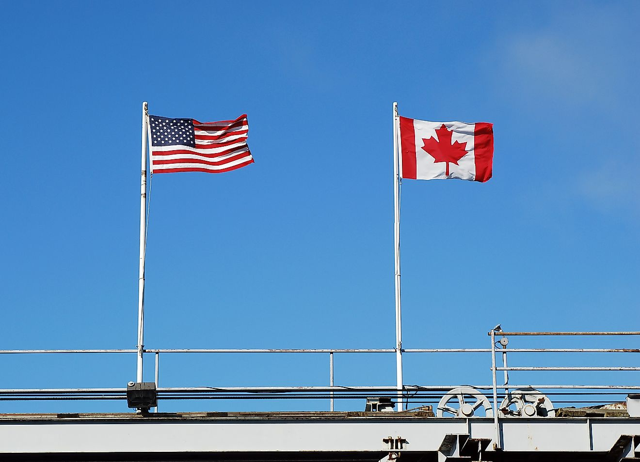 USA's and Canada's national flags fly at a US-Canada border. Image credit: Katherine Welles/Shutterstock.com
