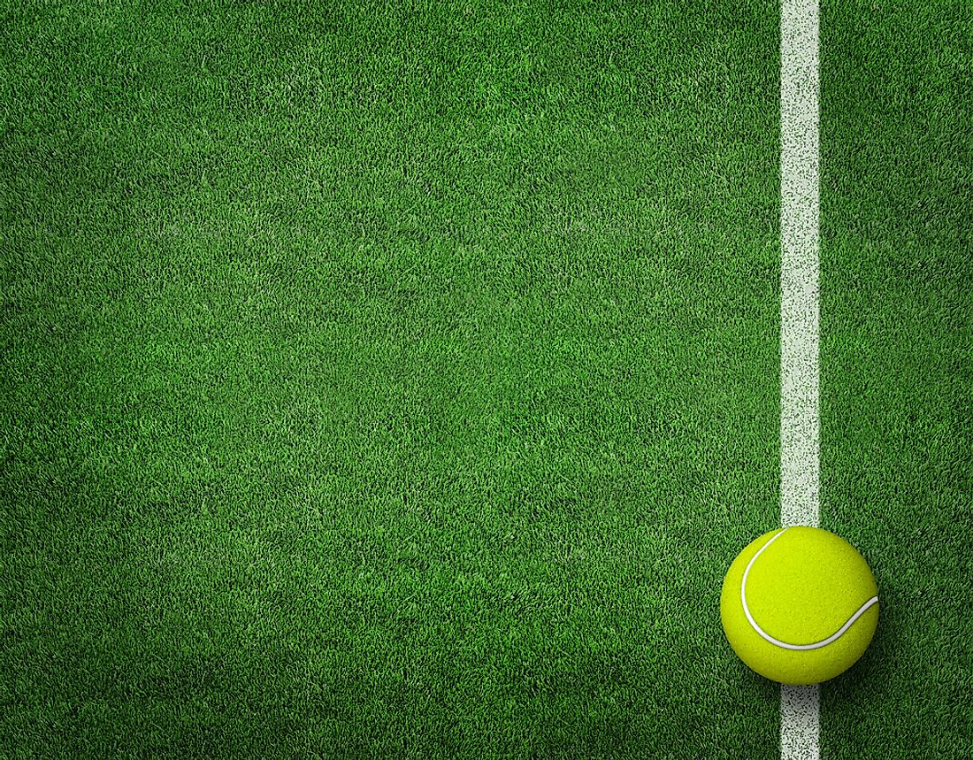 A tennis ball on a grass tennis court.