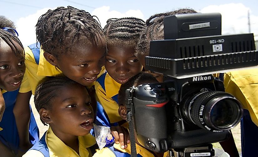Schoolchildren in Jamaica examining a camera. English is the main language used in imparting education in Jamaica.