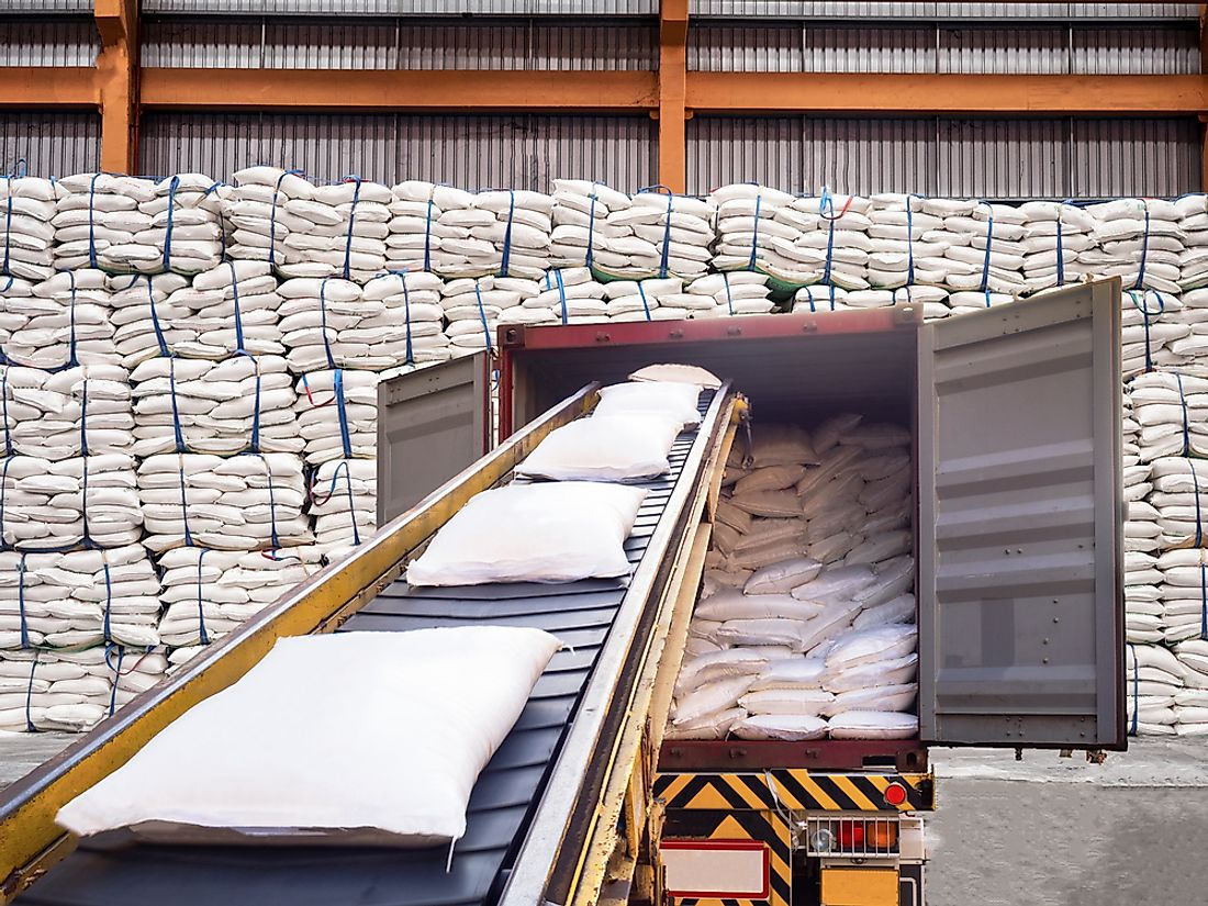 Bags of white sugar leave the warehouse.