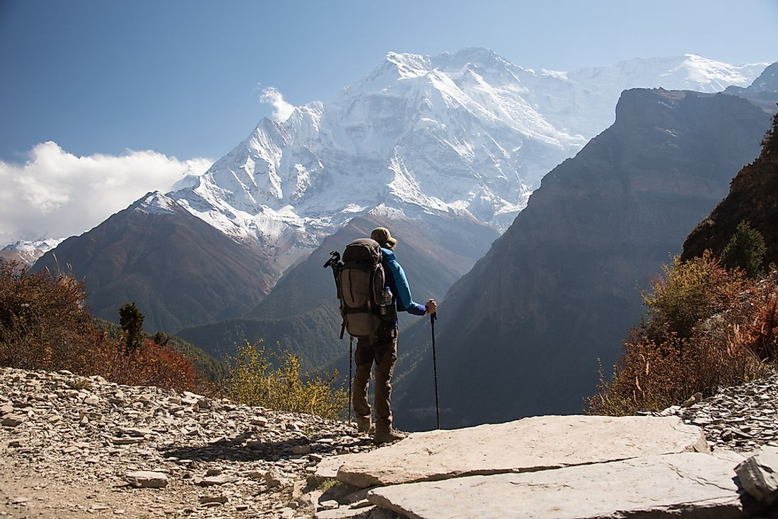 A backpacker stands overlooking the mountains in Nepal.