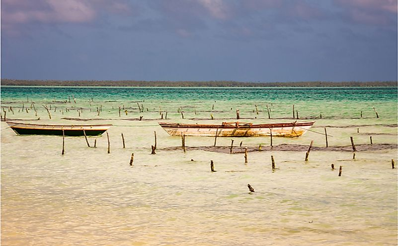 Old fishing boats in a shallow lagoon with turquoise water, Fanning Island, Kiribati Republic.