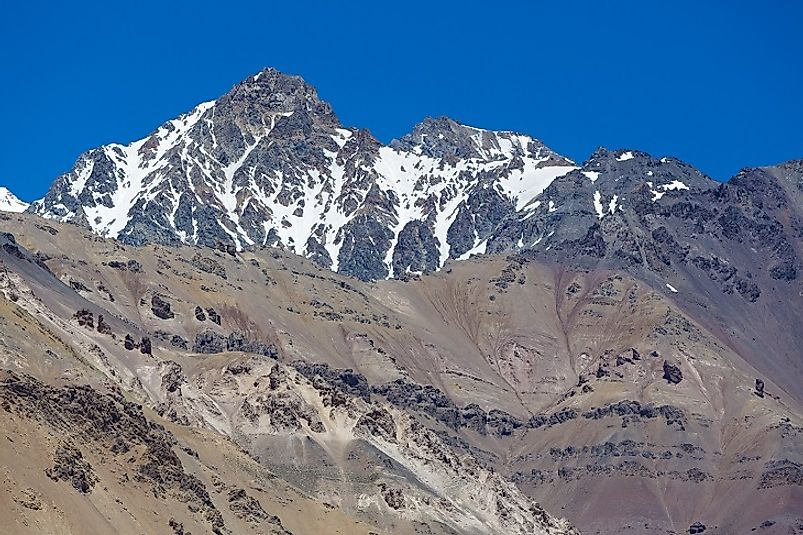The rock and snow of Mount Aconcagua reach up to meet the clear, blue Argentine skies. Due to the cold and dry clime, few plants grow here.