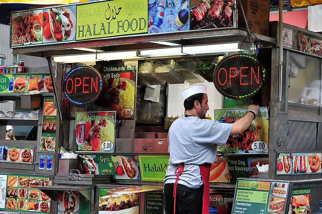 A food stall in New York advertising Halal food. Editorial credit: ChameleonsEye / Shutterstock.com.