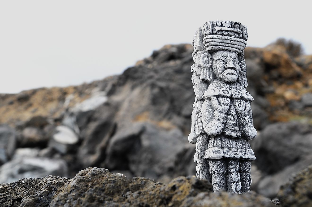 Ancient Maya statue on the rocks along the sea. Image credit: Underworld/Shutterstock.com