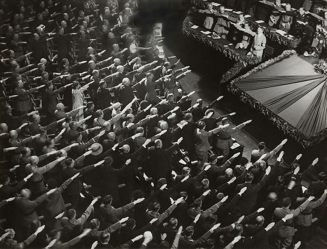 Attendees give Hitler the Nazi salute during the nation anthem, Oct. 9, 1935. They were meeting at the Kroll Opera in Berlin. Editorial credit: Everett Collection / Shutterstock.com