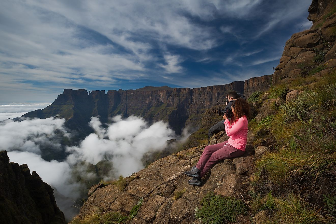 Two photographers photograph the beauty of the Drakensberg Amphitheatre from the Witches Viewpoint in the Ukhahlamba Drakensberg Park, South Africa. Image credit:  Rudi van den Heever/Shutterstock.com