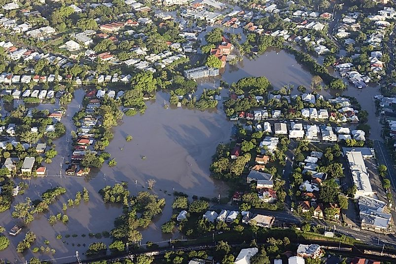 As climate change intensifies, coastal flooding, such as the pictured event in Brisbane, Australia from 2011, threatens to displace hundreds of millions of people.