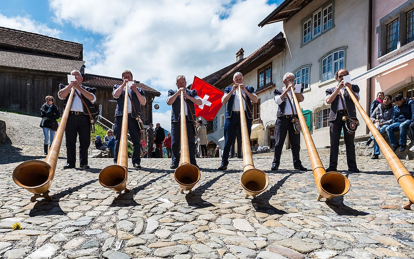 Swiss musicians play the alphorn, a traditional musical instrument on the main street of the Gruyere village. Image credit: eugeniek/Shutterstock.com