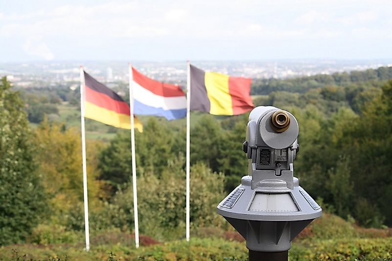 Flags of the Netherlands, Belgium, and Germany where the three countries meet atop Vaalserberg Hill.
