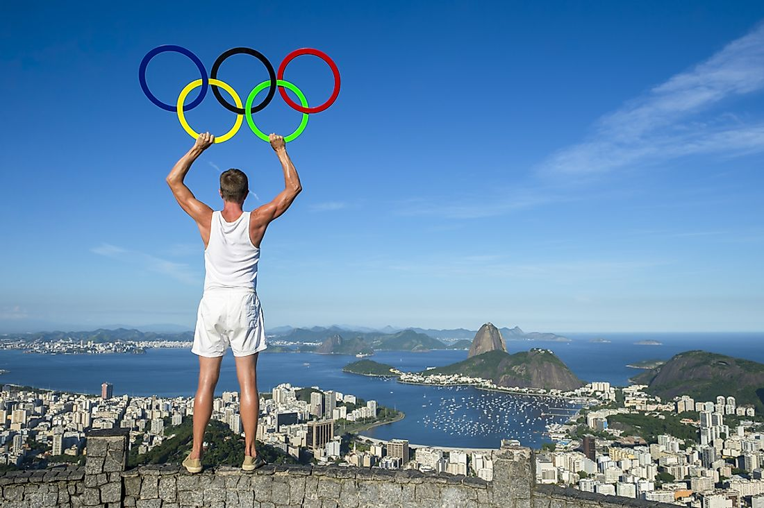 An athlete holds the Olympic rings while looking over Rio de Janeiro, Brazil. Editorial credit: lazyllama / Shutterstock.com.