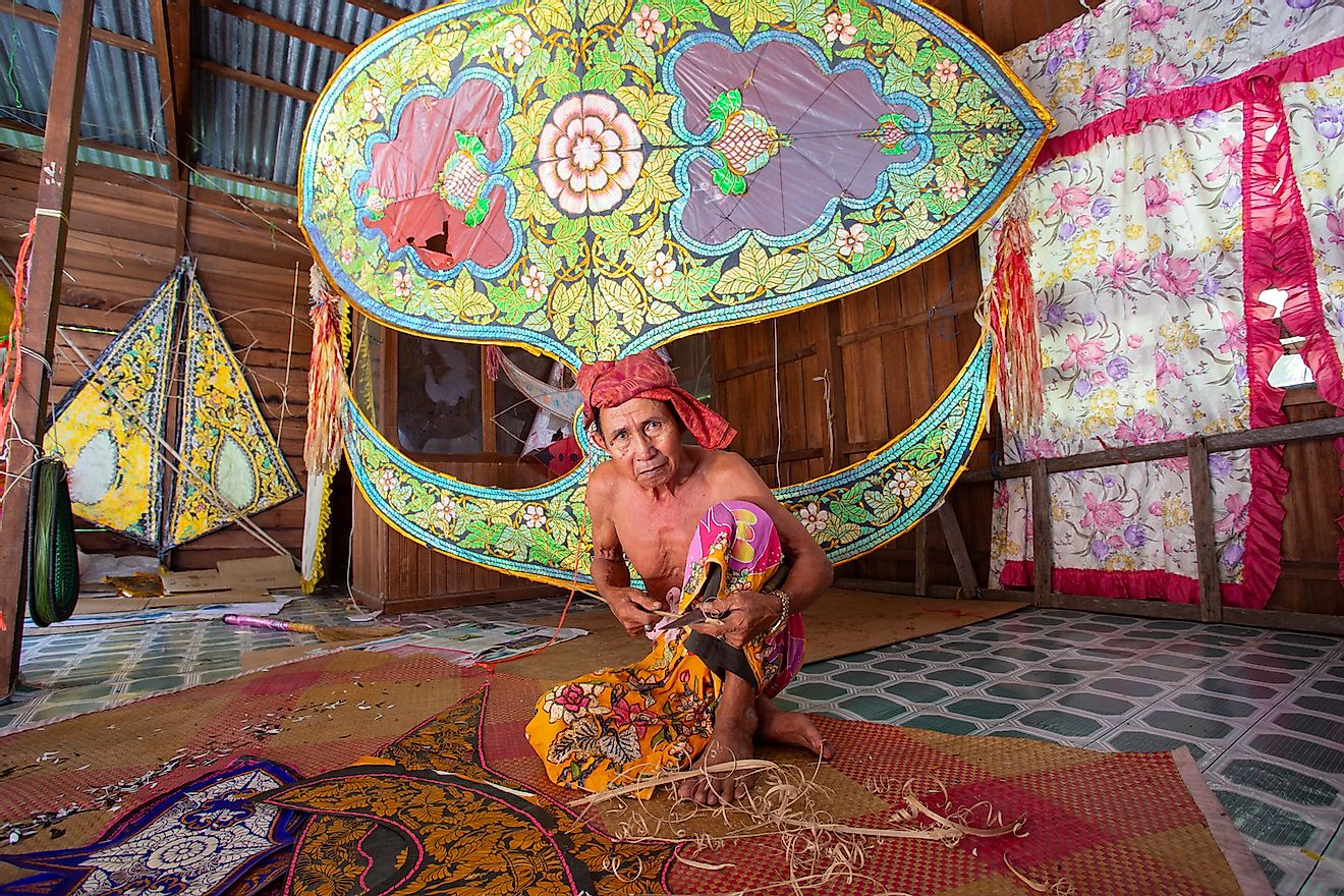 "A traditional kite or ""Wau"" maker wearing batik sarung (Malay tradisional skirt) working on a kite in his workshop. Image credit: udeyismail/Shutterstock.com"