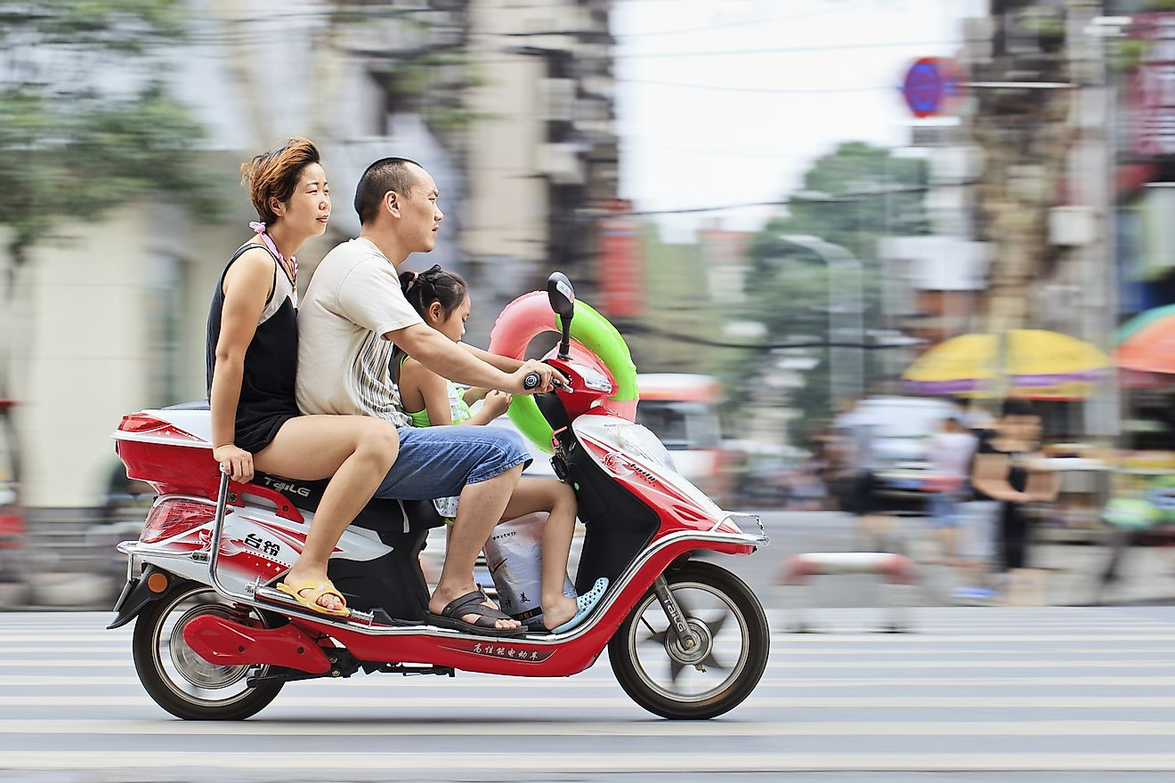 Chinese couple with their child on a scooter. Image credit: TonyV3112 / Shutterstock.com