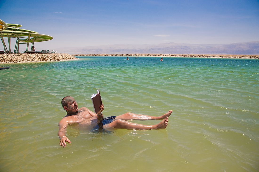 A man floating on the Dead Sea and reading a book.