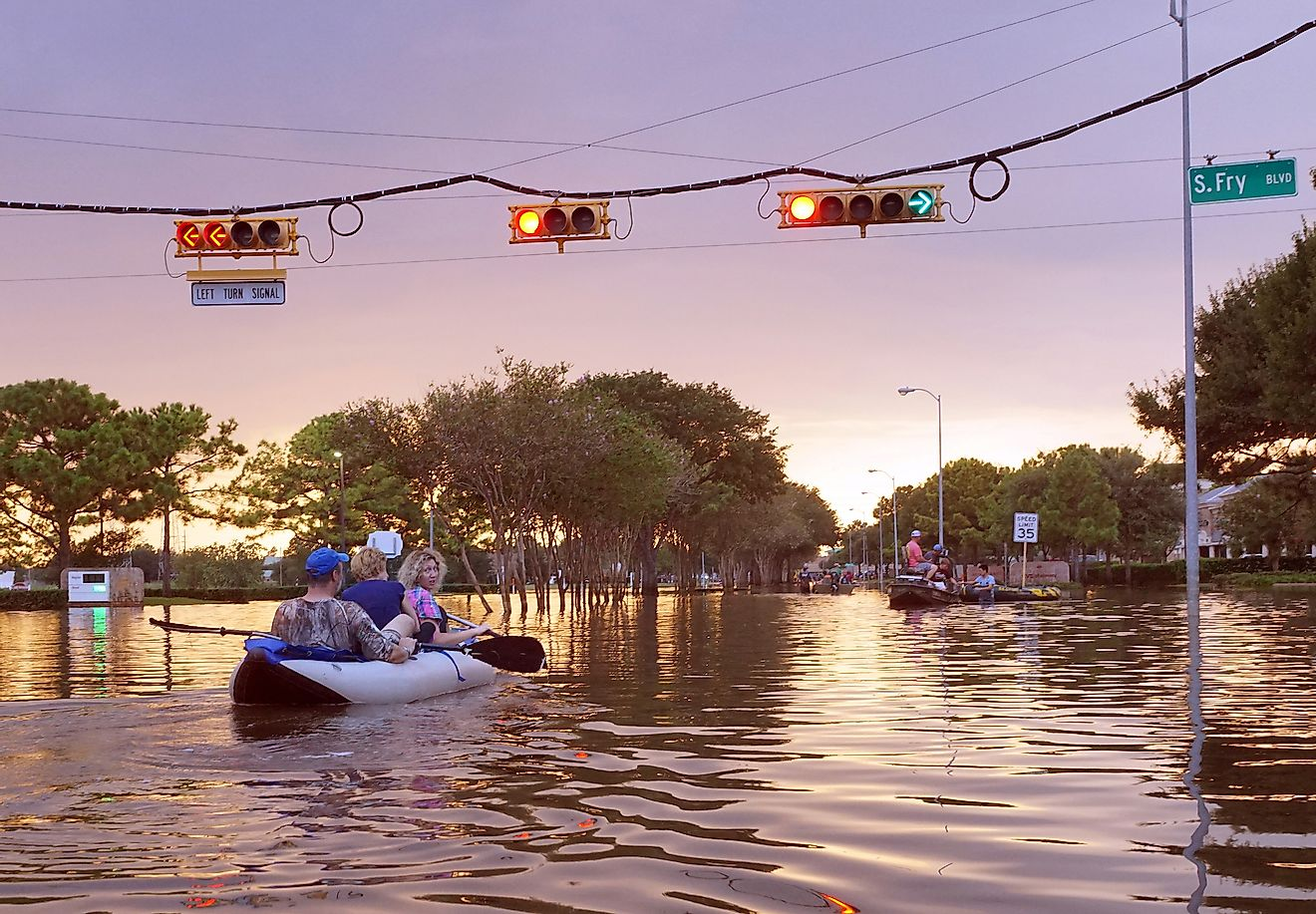 Traffic lights over flooded Houston streets and boats with people at sunset inTexas, USA. Image credit: Irina K/shutterstock.com