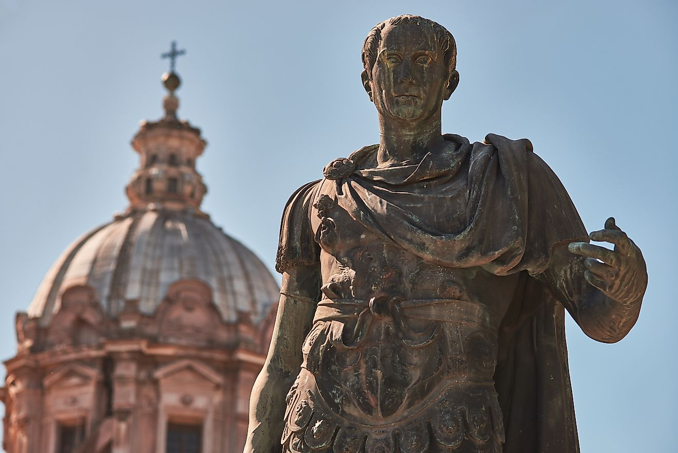 Bronze statue of emperor Julius Caesar, the dome of Saints Luca and Martina Church in the background. Image credit: Di Gregorio Giulio/Shutterstock.com