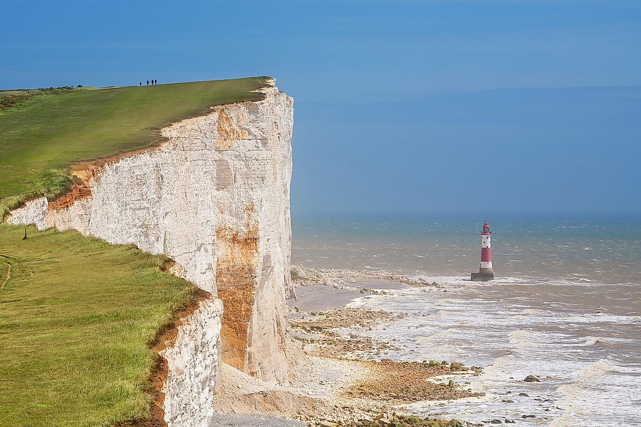 The world famous chalk cliffs at Beachy Head, with an offshore lighthouse below their base.