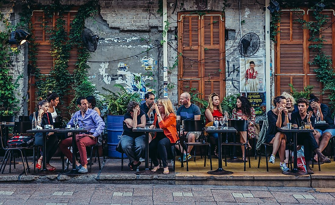 People at a cafe in Tel Aviv, Israel. Editorial credit: Fotokon / Shutterstock.com.
