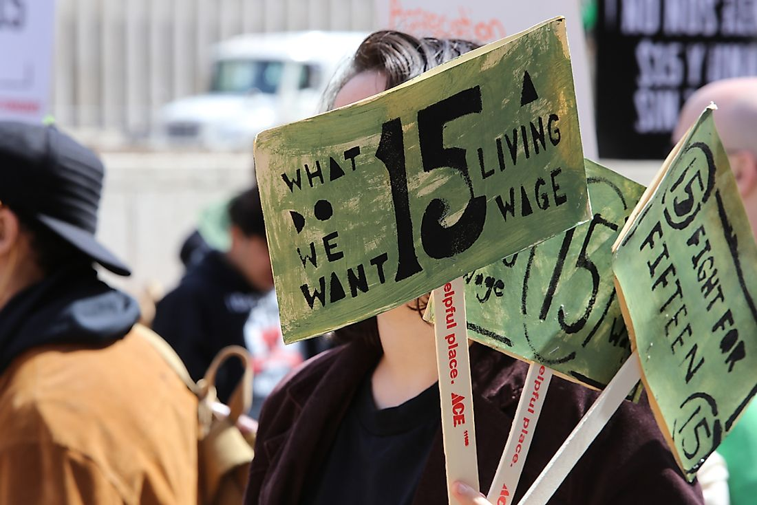 A protestor holds signs at a march for a $15 per hour federal minimum wage. Editorial credit: a katz / Shutterstock.com.