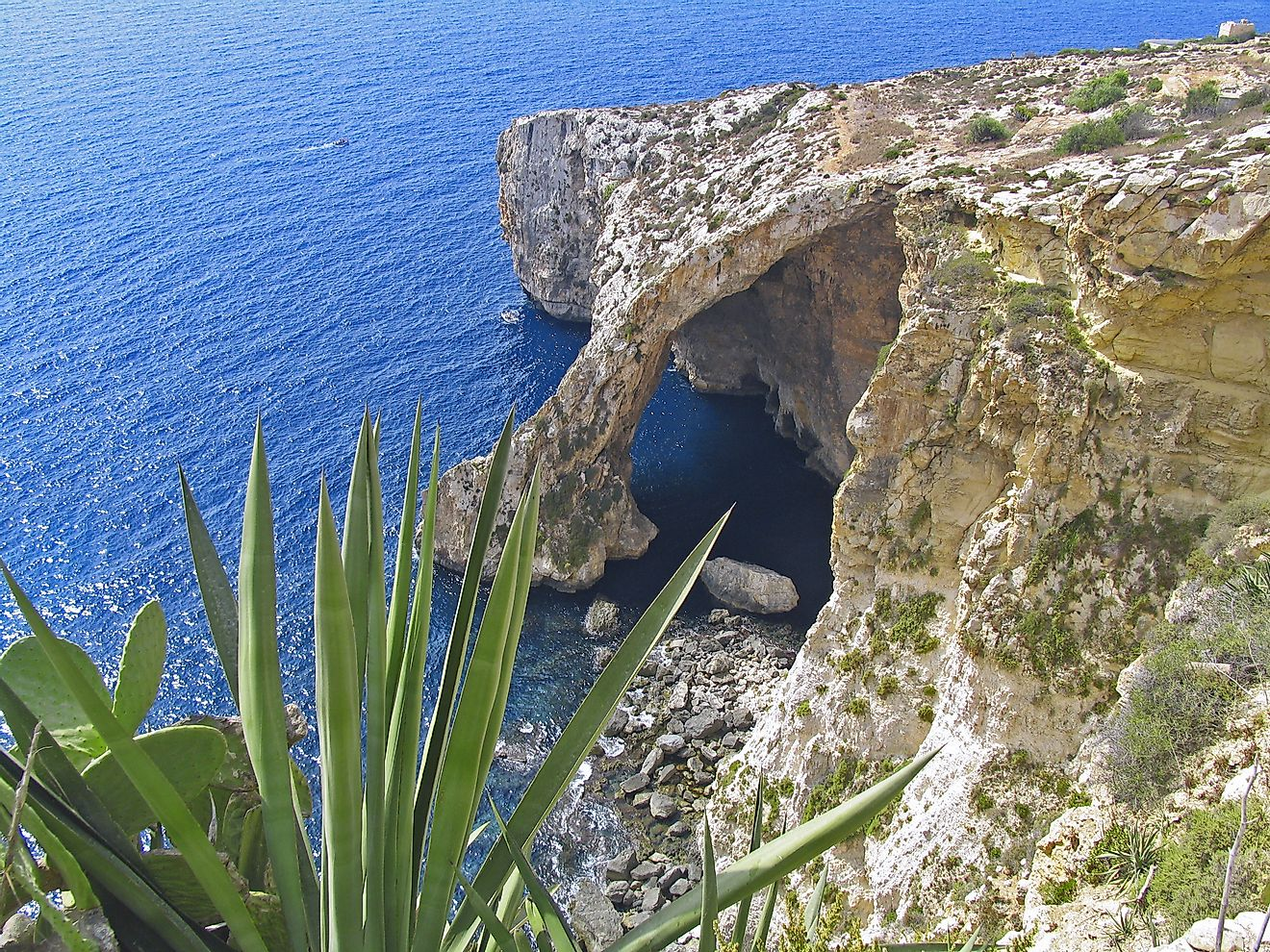 Il-Hnejja, the famous natural arch that extends over and into the waters of Malta's Blue Grotto.