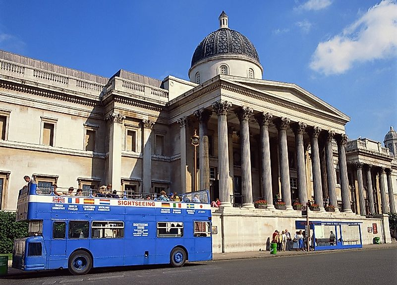A bus drops of eager tourists at the British National Gallery in London, England, United Kingdom.