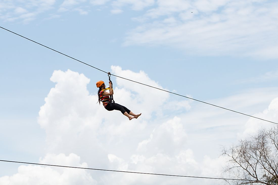 A woman rides on a zip-line.