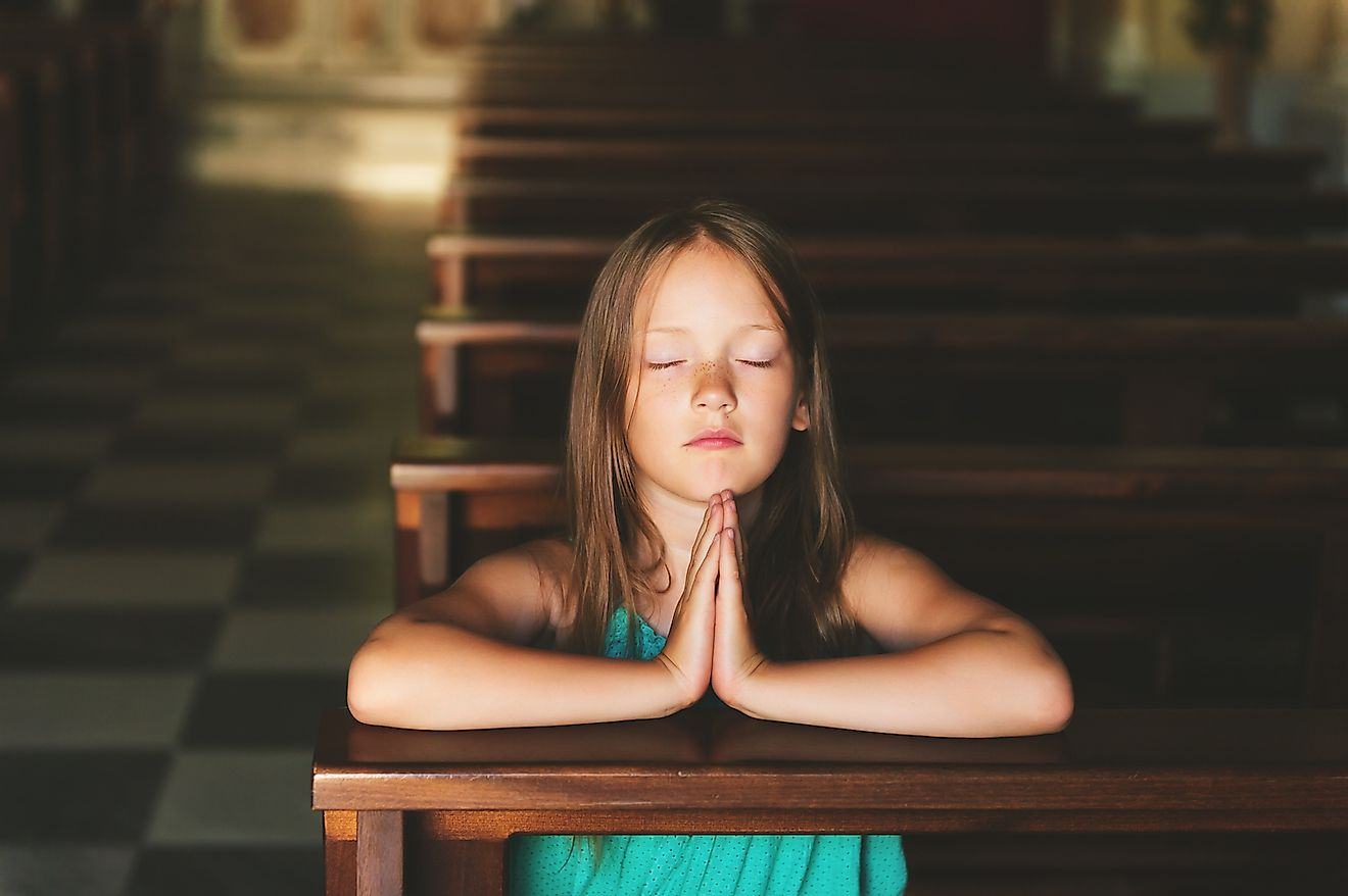 A child praying in church. Image credit: Anna Nahabed/Shutterstock.com