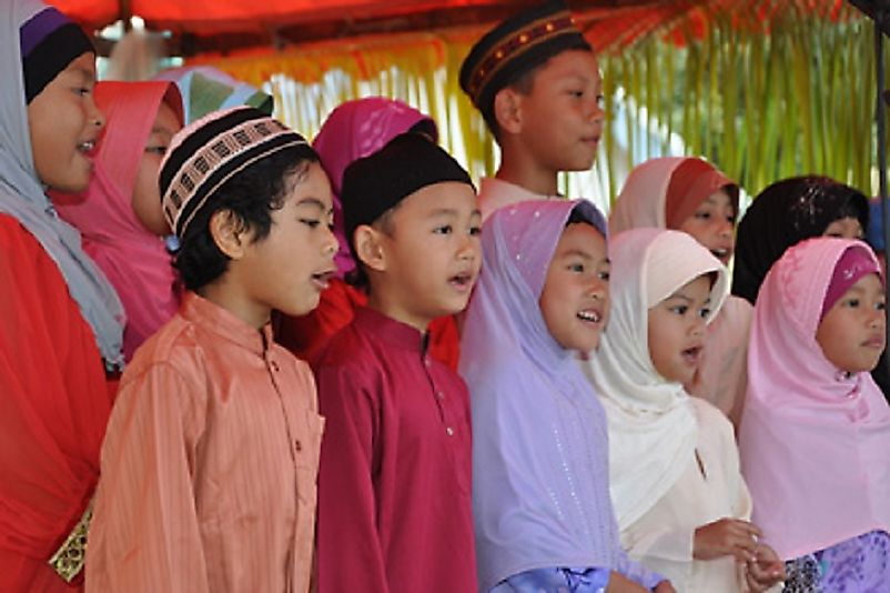 Cocos children dressed in traditional Malay attire and singing.
