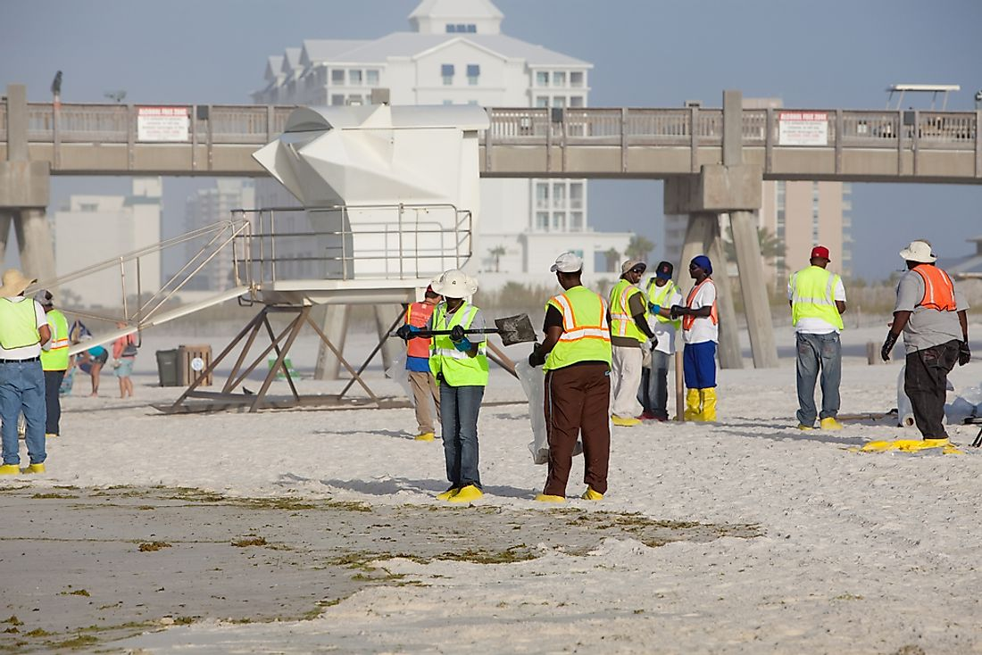 Workers clean up the aftermath of the BP oil spill in Florida in 2010. Editorial credit: Lorraine Kourafas / Shutterstock.com.