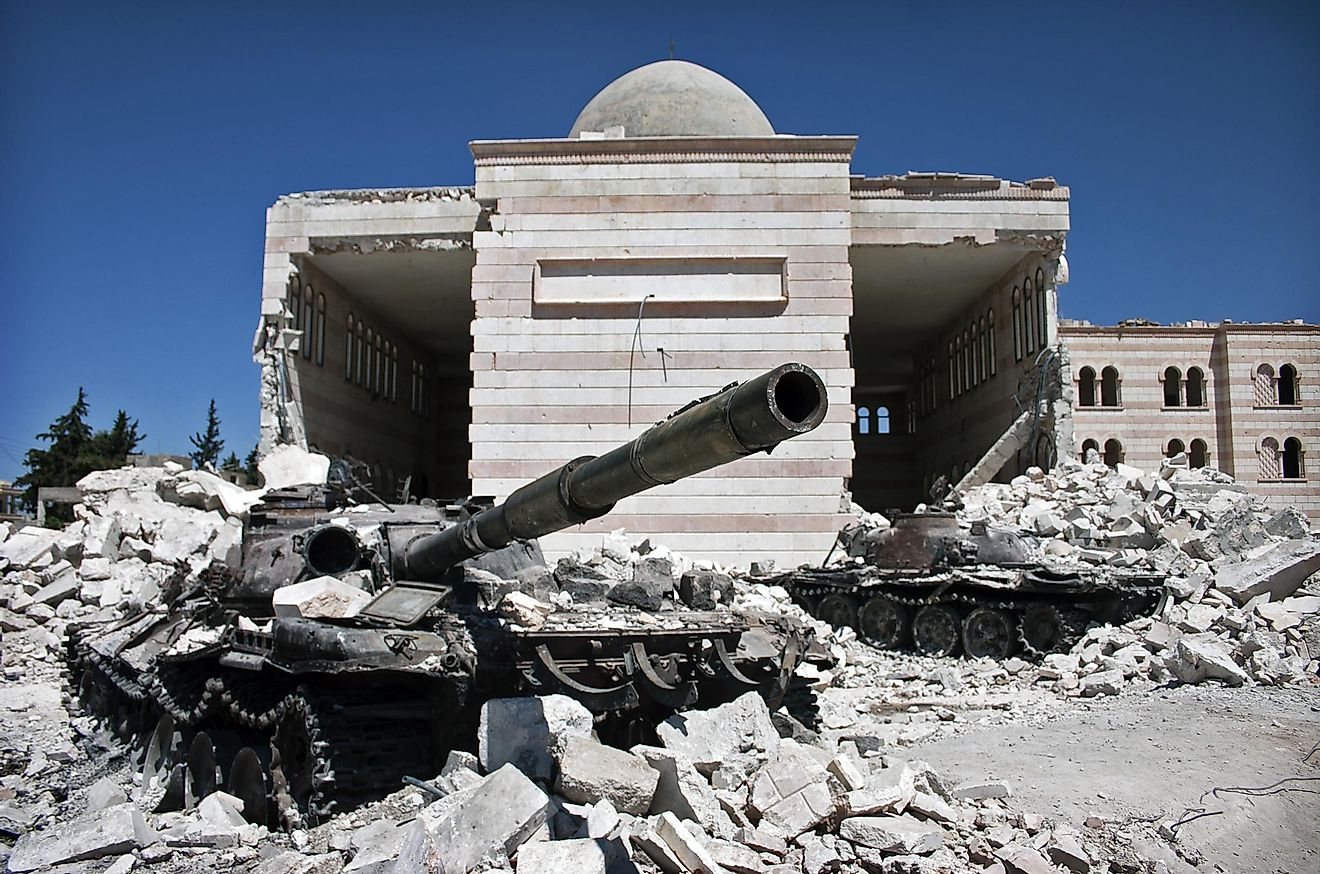A tank sits in front of a mosque that has been destroyed by civil war in Syria. Editorial credit: Christiaan Triebert / Shutterstock.com.