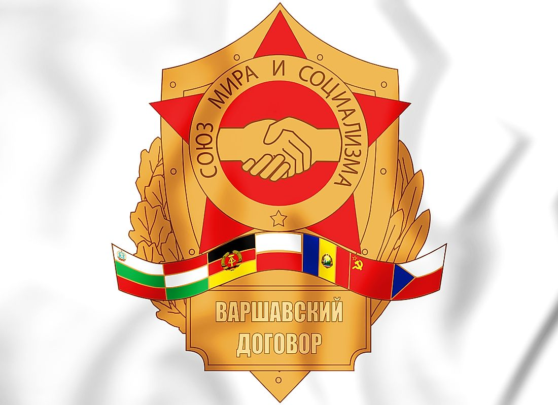 "Badge symbolizing the Warsaw Pact and its ""Union of peace and socialism"", depicting the flags of the signatory nations and shaking hands."