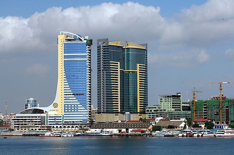 Massive Tanzanian skyscrapers dwarf the boats in Dar es Salaam's Indian Ocean harbor below them.