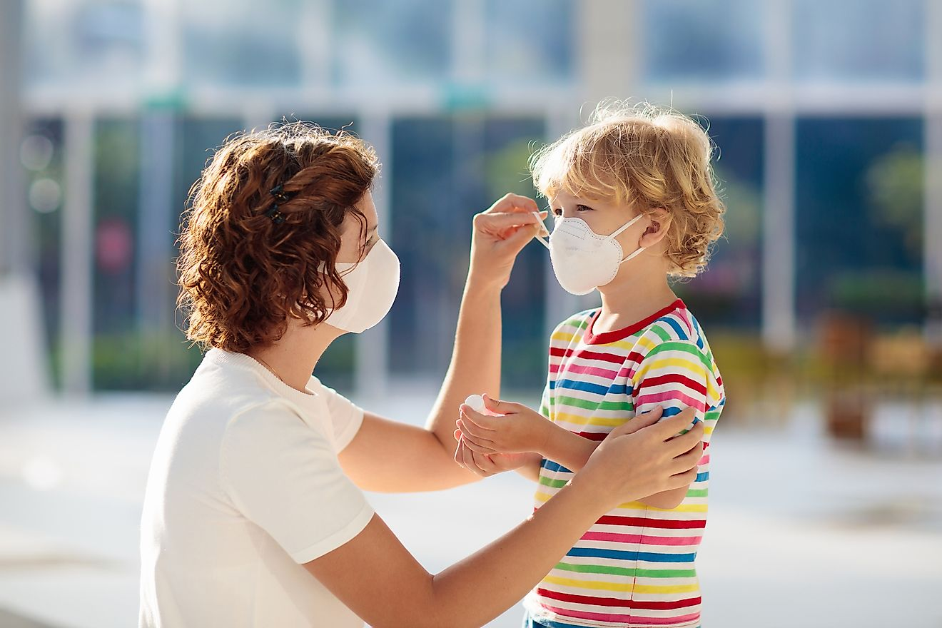 A mother helps her son put on a face mask as a precaution to combat the COVID-19. Image credit: FamVeld/Shutterstock.com