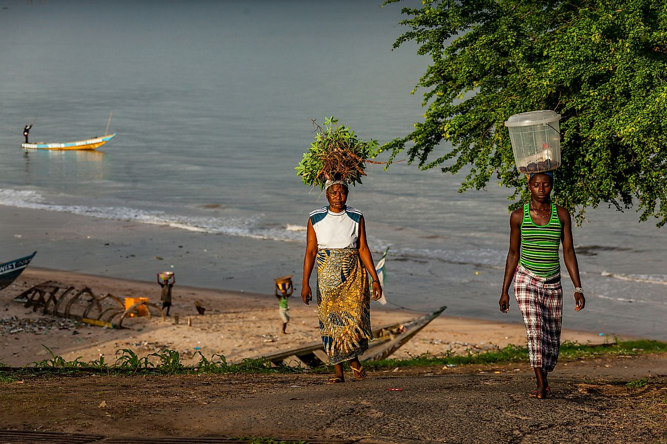 Two people with vegetables on head along a beach in Yongoro, Sierra Leone. Image credit: robertonencini/Shutterstock.com.