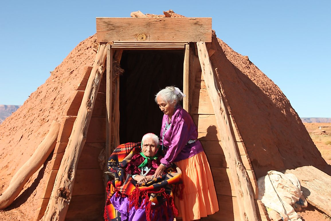 Two Navajo women outside a hogan, the traditional dwelling of the Navajo.