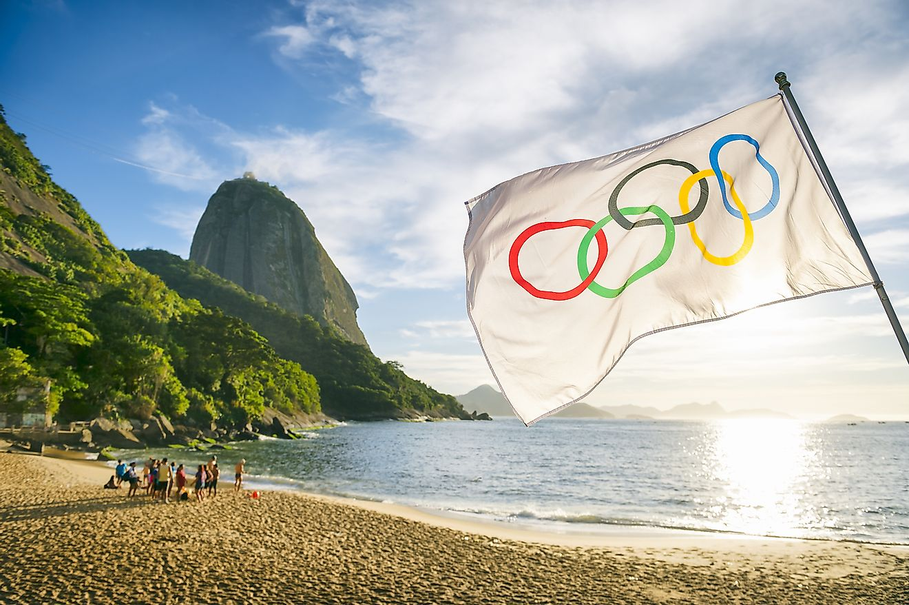 Olympic flag waves in front of the rising sun at Red Beach during the 2016 Summer Games.