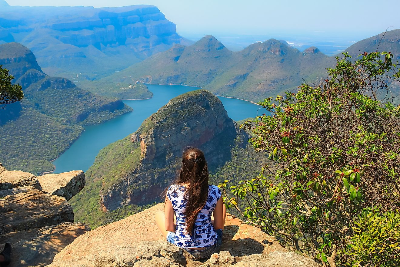Girl sitting on stone on the cliff in the Blyde River Canyon, South Africa. Image credit: GuilhermeMesquita/Shutterstock.com