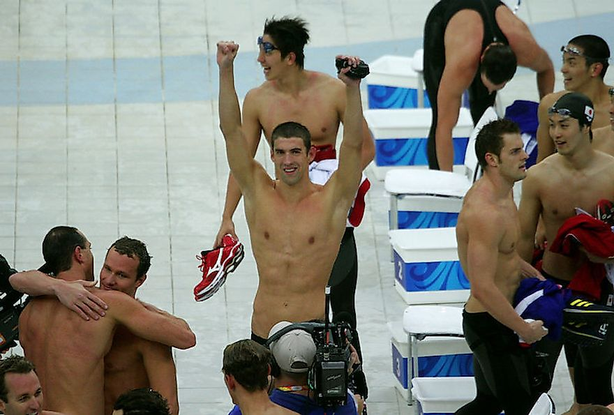 Michael Phelps (with his hands raised) celebrates with his teammates after winning his 8th gold medal.