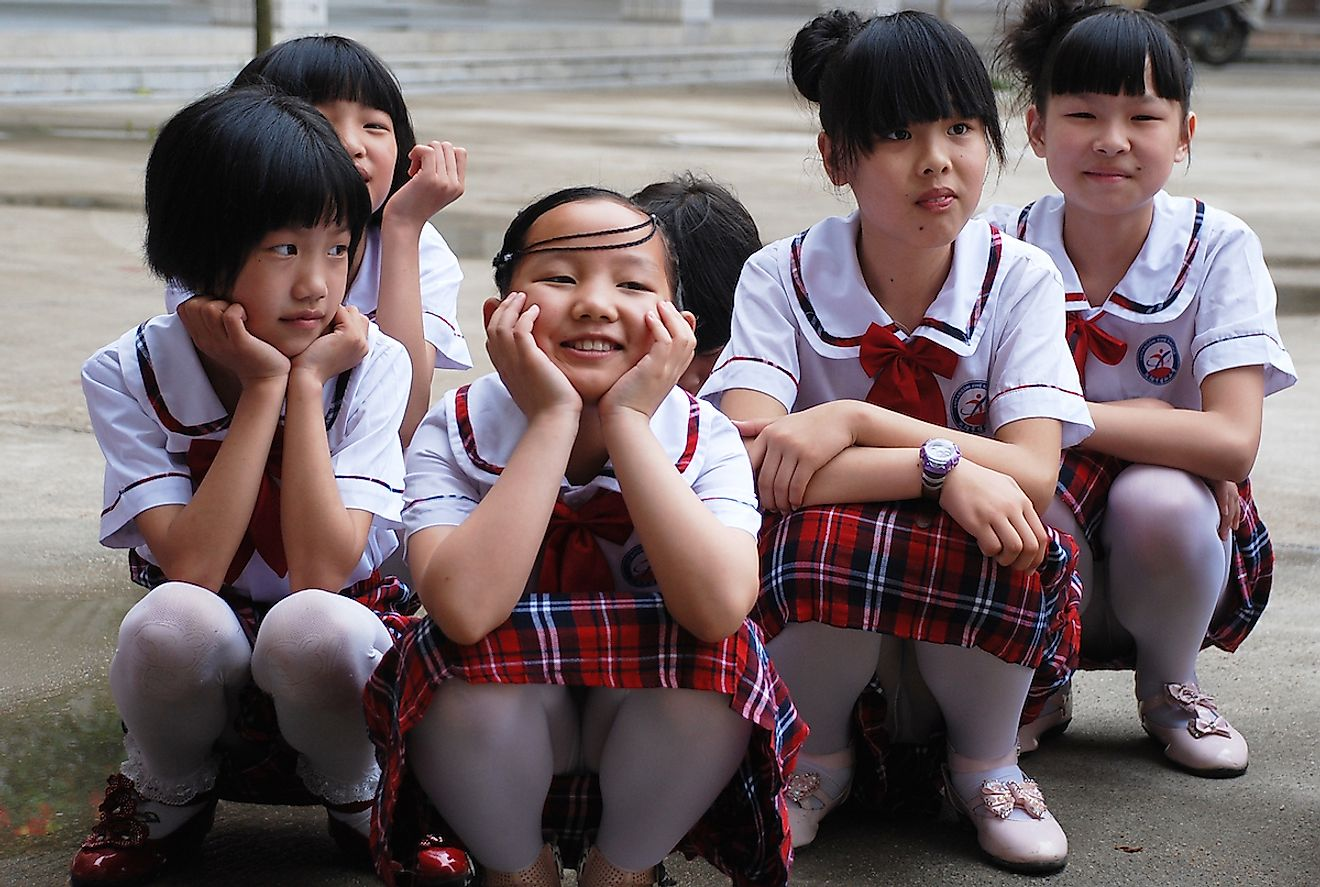 Group of Chinese school girls squatting in their school yard in Liuyang, China. Image credit: Drevs/Shutterstock.com
